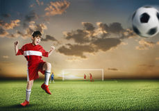 Young football champion. Excited boy football player at stadium kicking ball Stock Image
