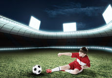 Young football champion. Excited boy football player at stadium kicking ball Royalty Free Stock Photos