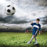 Young football champion. Excited boy football player at stadium kicking ball Stock Photography