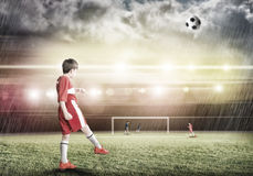 Young football champion. Excited boy football player at stadium kicking ball Stock Photos
