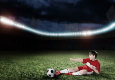 Young football champion. Excited boy football player at stadium kicking ball Royalty Free Stock Photography