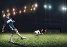 Young football champion. Excited boy football player at stadium kicking ball Royalty Free Stock Images