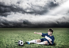 Young football champion. Excited boy football player at stadium kicking ball Royalty Free Stock Image