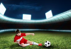 Young football champion. Excited boy football player at stadium kicking ball Stock Images