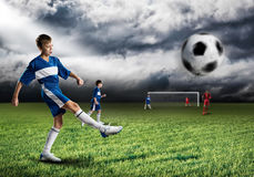 Young football champion. Excited boy football player at stadium kicking ball Royalty Free Stock Photo