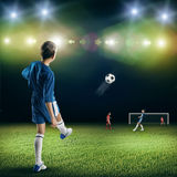 Young football champion. Excited boy football player at stadium kicking ball Stock Photo