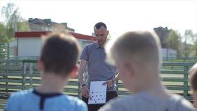 Young Football coach trainer coaching kids using tactic strategy magnetic whiteboard. Soccer trainer explaining match. Tactics to children soccer team stock video footage