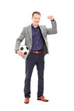 Young football fan cheering with ball in hand Royalty Free Stock Photos