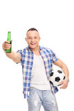Young football fan holding a beer and cheering. Vertical shot of a young football fan holding a beer, cheering and looking at the camera isolated on white Stock Photo