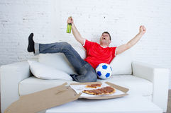 Young football fan man watching game on tv in team jersey celebrating goal crazy happy on couch Stock Photo
