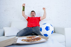 Young football fan man watching game on tv in team jersey celebrating goal crazy happy on couch Royalty Free Stock Image