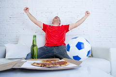 Young football fan man watching game on tv in team jersey celebrating goal crazy happy on couch Stock Photos
