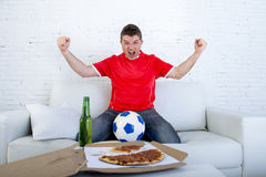 Young football fan man watching game on tv in team jersey celebrating goal crazy happy on couch Stock Photography