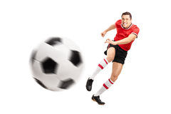 Young football player kicking a ball hard Royalty Free Stock Image