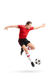 Young football player kicking a ball in mid-air Stock Photos
