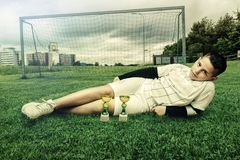 Young football player laying on grass Stock Photos