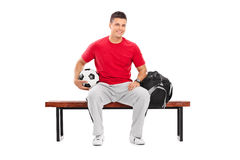Young football player sitting on a bench Royalty Free Stock Image