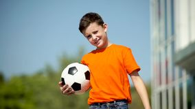 The young football player waves a hand and invites in a game stock video footage