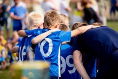 Young football players in blue jersey sportswear. Group photo with football coach. Young sports team with football coach royalty free stock photo