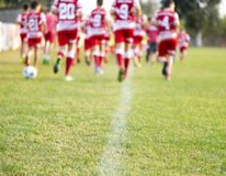 Young football players runing in red and white shirts stock images