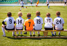 Young Football Players. Young Soccer Team Sitting on Wooden Bench Stock Image