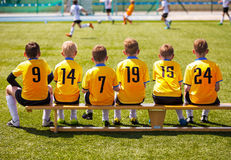 Young Football Players. Young Soccer Team Sitting on Wooden Bench royalty free stock photo