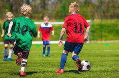 Young football soccer players running and kicking ball on sports Stock Photo