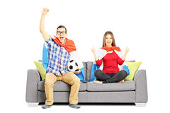 Young football supporters sitting on a modern sofa Royalty Free Stock Photography