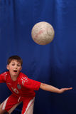 Young footballer. In a red sport shirt on a dark blue background pulls ball a head Royalty Free Stock Photo