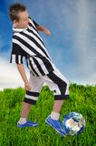 Young footballer with Earth ball on grass Stock Images