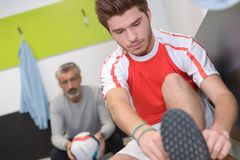 Young footballer putting on boots Royalty Free Stock Photo