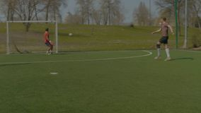Young footballer shooting on goal during training stock video footage