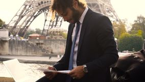 Arabian student preparing before exams near Eiffel Tower with laptop in slow motion. Young foreign boy planning study in France and reading instructions to exam stock footage