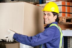 Young Foreman Lifting Cardboard Box Stock Photo