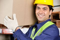 Young Foreman Lifting Cardboard Box Royalty Free Stock Image