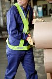 Young Foreman Working At Warehouse. Midsection of young foreman in uniform working at warehouse Royalty Free Stock Image