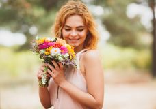 Young woman smiling with flowers in hands. Beautiful coniferous forest in the background. background blur. Royalty Free Stock Photo
