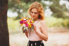Young woman smiling with flowers in hands. Beautiful coniferous forest in the background. background blur. royalty free stock photos