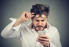 Confused man reading phone with difficulties. Young formal man reading smartphone and having problems with eyesight squinting on gray background stock photos