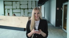 Young formal woman using smartphone in office. Stylish blond woman in jacket standing in contemporary office hall and. Stylish blond woman in jacket standing in stock footage