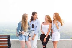 Young four student girls talking in the Park after College. Women smile, rejoice, have fun on the background stock photos