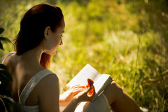 Young foxy haired woman reading book in nature. Rear view of attractive woman sitting on grass with book in her hands. Young foxy haired woman reading book in Stock Photo