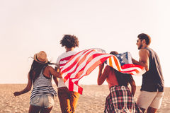 Young and free. Rear view of four young people carrying american flag while running outdoors Royalty Free Stock Photo