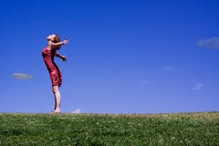 Young free woman outstretched against bluesky. Beautiful woman stretching arms on a hillside against slightly cloudy blue skies in this summer image Royalty Free Stock Image