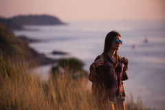 Young freedom woman enjoy ocean sunset on mountain peak Stock Images