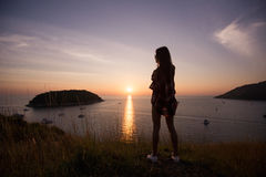 Young freedom woman enjoy ocean sunset on mountain peak Stock Photo