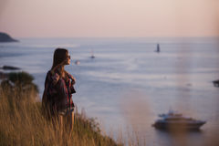 Young freedom woman enjoy ocean sunset on mountain peak Stock Photos