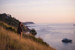 Young freedom woman enjoy ocean sunset on mountain peak Stock Photography
