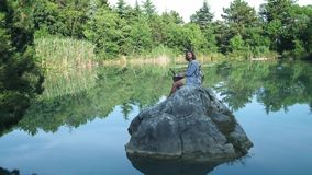 A young freelance guy sits on a stone in the middle of a lake with a laptop. Freelance concept. Work on travel. Wireless