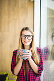 Young freelance lady drinking coffee in casual clothes and looking at camera near a window. Morning. Royalty Free Stock Photos